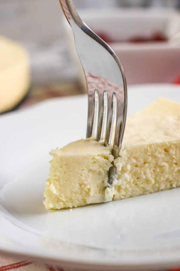 fork taking bite of cheesecake